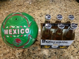 A six pack of Corona next to a Mexican soccer ball